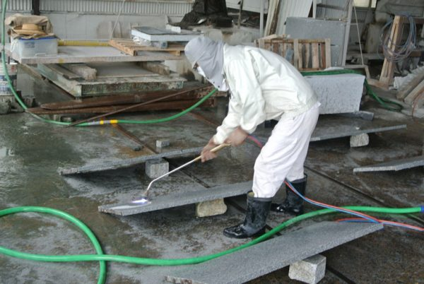 福島県産の青葉みかげ石にバーナー加工をしている様子